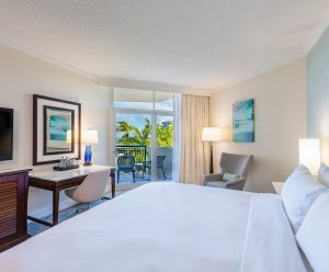 Ocean view room with a king bed, desk and chair, looking out on to the private balcony